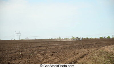 The tractor sows seeds of sunflower field - Tractor with...