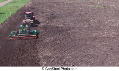 The tractor sows the field. Top view appears in the frame