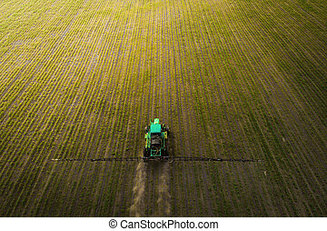 The tractor spraying the field with chemicals in the spring