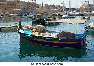 The traditional Maltese boat (Luzzu) moored in the Kalkara creek. Malta
