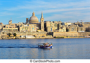 The traditional Maltese Luzzu boat for tourists cruises and view on Valletta, Sliema, Malta