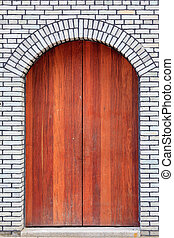 The traditional  wooden arched door and brick wall,which has the
