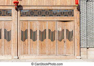 The traditional  wooden door with lattice windows and red lanterns hanging during Chinese new year,which has the style of typical architecture of southern China in the Ming and Qing Dynasties.
