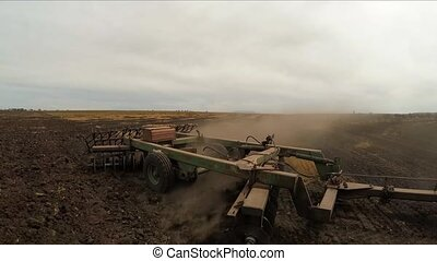 The trailer plow plows the land on the field. Slow motion. -...