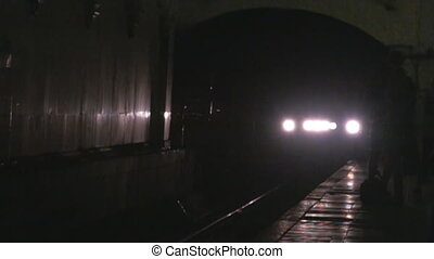 train enters the station from a dark subway tunnel