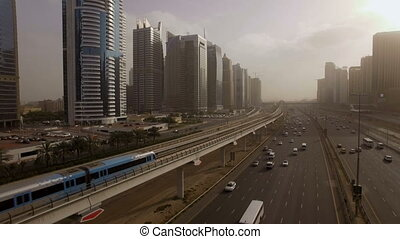the train goes over the viaduct, along the highway among the skyscrapers in Dubai, UAE