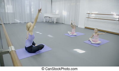 The trainer and two girls sit tailor-fashion on the mats in the ballet class.