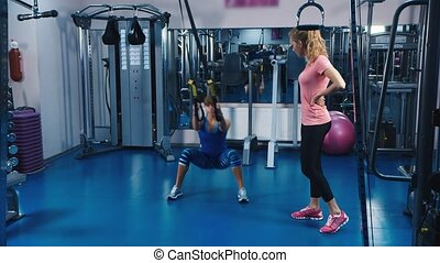 The trainer shows exercises in fitness club