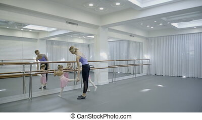 The trainer teaches two girls how to turn around beautifully while ballet class