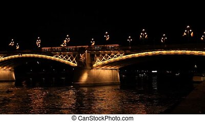 The tram rides on the night bridge in Budapest