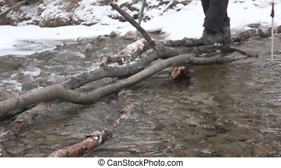 Trekker traveller overcomes a water barrier. - The...
