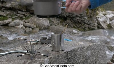 The traveler removes a pot from a gas burner, and pours boiling water into a mug. He makes tea. Close-up