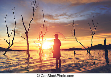 the tree , sun, cloud and water to be landscape. the mountain are background the lake. A man hold umbrella in the water.