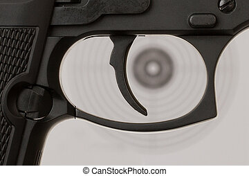 The trigger of a handgun with a shooting target