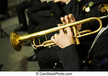 The trumpeter is playing on a silver trumpet. Trumpet players