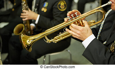 The trumpeter is playing on a silver trumpet. Trumpet players.