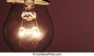 The Tungsten Filament in a Glass Lamp Close-up in Slow Motion on Red Background