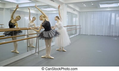 The two ballerinas are doing right leans with raised hand...