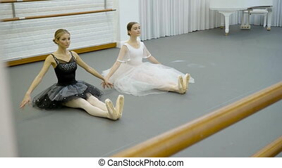 The two ballerinas do point toes sitting on the floor with...