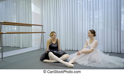 The two ballerinas sit on the floor in the bright studion...