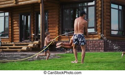 The two boys are playing with mom and dad in the backyard of their house drenching with hose water and laughing and smiling in slow motion. Happy family