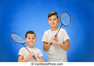 The two boys with badminton rackets outdoors - Boys with...