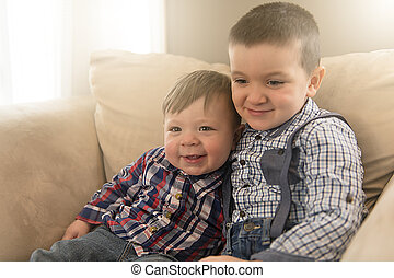two brothers sitting embracing on the couch