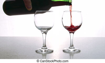The two cristall glasses is being fulfilled with the red dry...