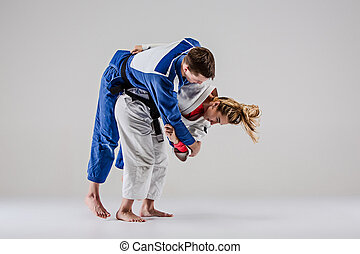 The two judokas fighters posing on gray - The two judokas...