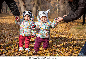 The two little baby girls standing in autumn leaves