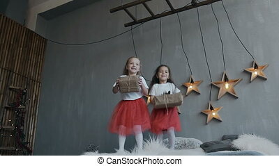 The two little sisters of the twin actively have fun at the bed of their parents. Children dressed in identical red skirts, jump on the bed with Christmas gifts in their hands