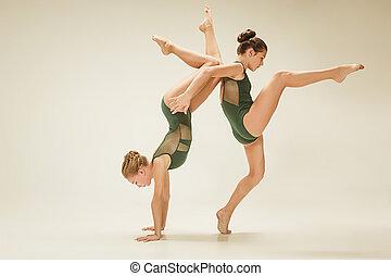 The two modern ballet dancers dancing on gray studio...