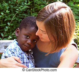 Young Caucasian woman hugging an African American child.