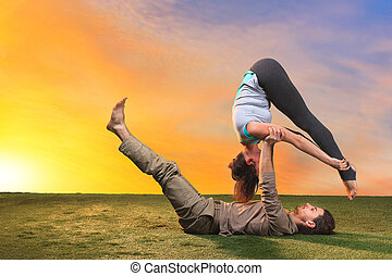 The two people doing yoga exercises against sunset sky