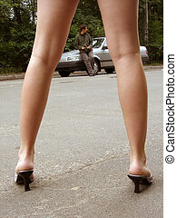 The female legs against the car and man