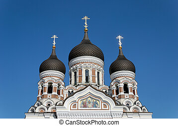 The upper part of St. Alexander Nevsky Cathedral in Tallinn, Estonia with golden crosses glowing in the evening sun.