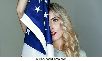 The US flag is in the hands of a brilliant blonde. Posing in...