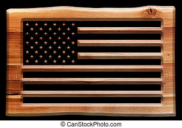The USA flag cut in a wooden board, plate isolated on black.