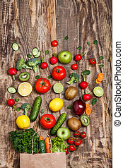 The vegetables from a paper bag on wooden table