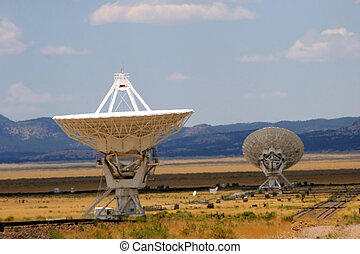 Heat waves eminating from the New Mexico desert floor shimmer around the huge dishes of the Very Large Array. The array listens to the cosmos seeking to find evidence of intelligent life elsewhere in the galaxy.