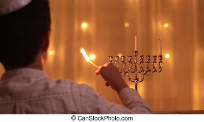 the view from the back of a young boy lights the first candle of the menorah during the Jewish holiday of Hanukkah