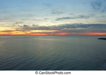 The view from the height over the sea with a beautiful dramatic sunset.