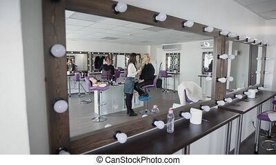 The view from the mirror with lights, which is located in a light dressing room. Two make-up artist doing makeup young model, who quietly wait for completion by this stage and start working with hair