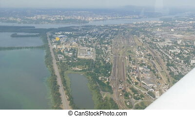 The view from the window of the porthole of a small passenger plane against a white wing. Top view of the metropolis is a large green river on the banks of which houses are built. Small cars.