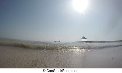 The view from water level of the sea beach on a breakwater with an arbor and the boat moving by the tropical sea, a wave runs on the camera