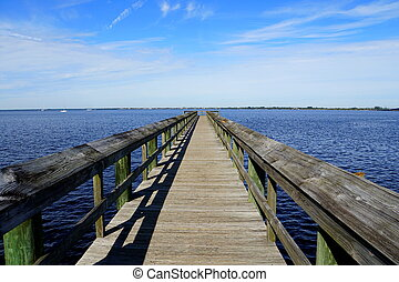 The view of a wooden pier by the blue ocean near Punta Gorda, Florida, U.S.A