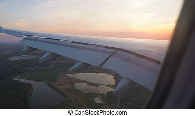 the view of the sunset from the window of the plane. wing in the sun. air flight