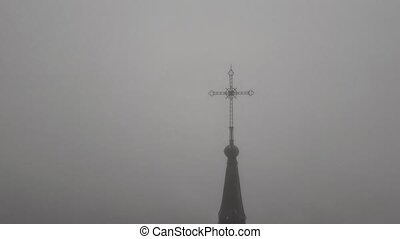 The view on cross in the fog on church in Riga.