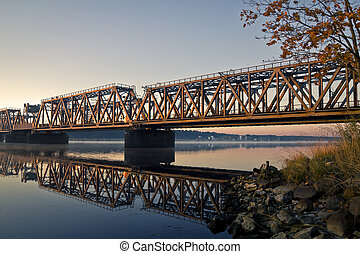 The view on train bridge above the river during sunrise.