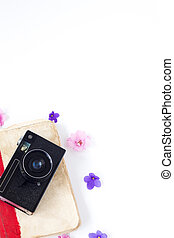 the vintage film camera old book flower and tea on white background .